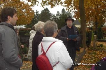 """Gerhard H. Gräber (mit Hut) beim darbieten seiner illustren Geschichten über den """"Alten Friedhof""""."""