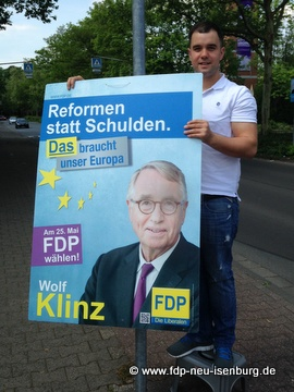 Daniel Wilkening beim Aufhängen von FDP-Wahlplakaten in Gravenbruch.