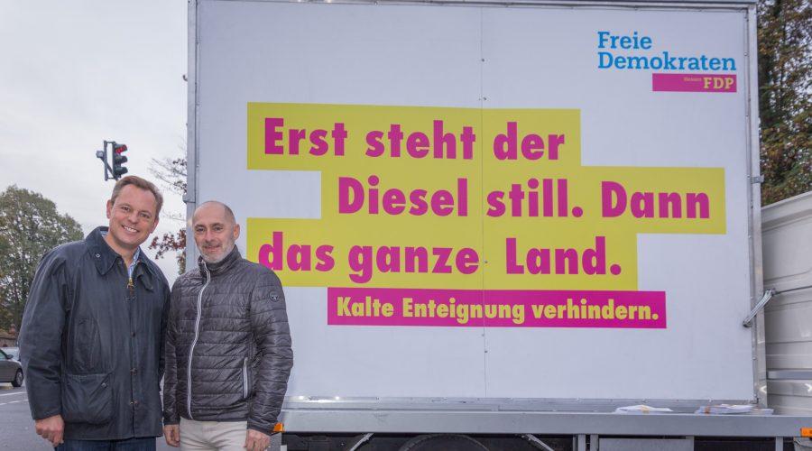 """Thilo Seipel (li.) und Spitzenkandidat René Rock (re.) vor dem rollenden """"Wesselmann""""."""